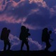 Three Youth Backpackers Against Sunset